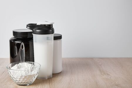 sports bottle with protein shake near jars isolated on grey