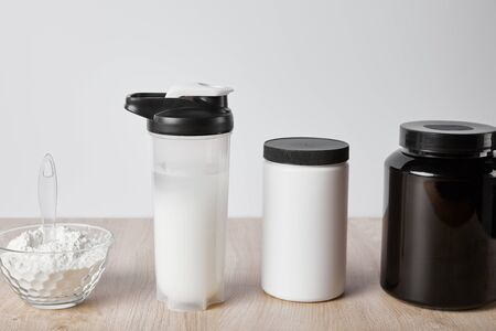 protein shake in sports bottle near jars isolated on grey