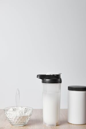 protein shake in sports bottle near jar and glass bowl with protein shake isolated on grey