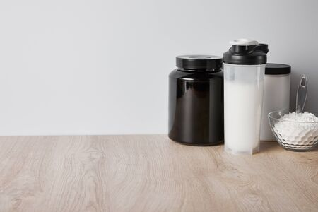 protein shake in sports bottle near jars and glass bowl with protein powder isolated on grey Imagens