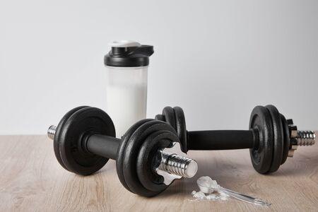 Löffel mit Proteinpulver in der Nähe von Hanteln und Sportflasche isoliert auf Grau