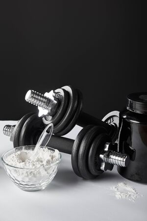 glass bowl with protein powder near dumbbells on black Imagens