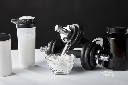 glass bowl near sports bottle with protein shake on black