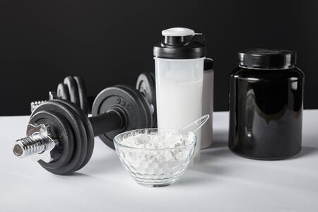selective focus of bowl near dumbbells and sports bottle with protein shake on black