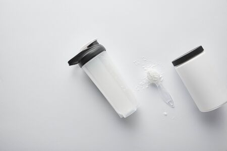 top view of jar near sports bottle and spoon with protein on white