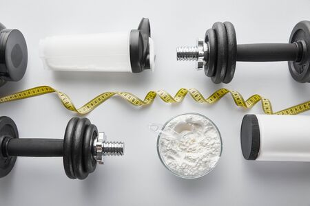 top view of heavy dumbbells near sports bottle and measuring tape on white Imagens