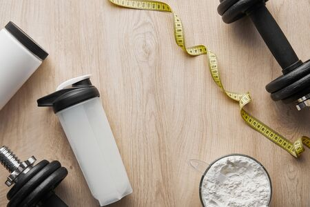 top view of dumbbells near sports bottle and measuring tape on wooden surface