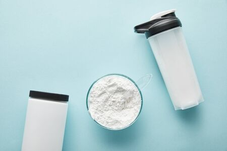 top view of sports bottle near jar and glass bowl with protein powder on blue
