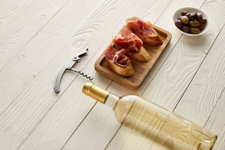 bottle with white wine near prosciutto on baguette, olives and corkscrew on white wooden surface