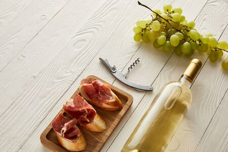bottle with white wine near grape, prosciutto on baguette and corkscrew on white wooden surface