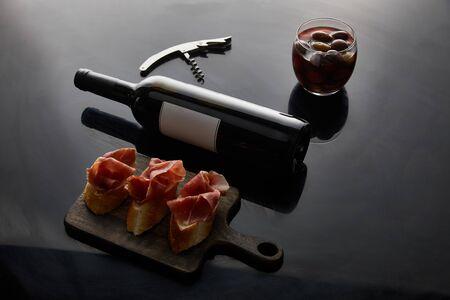 wine bottle with blank label near sliced prosciutto on baguette, corkscrew and olives on black background Reklamní fotografie