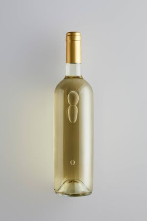 top view of bottle with white wine on white background