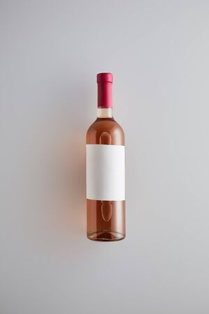 top view of bottle with rose wine and blank label on white background