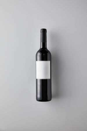 top view of bottle with red wine and blank label on white background