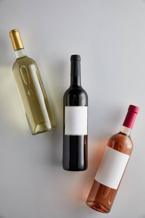 top view of bottles with white, red and rose wine on white background Imagens