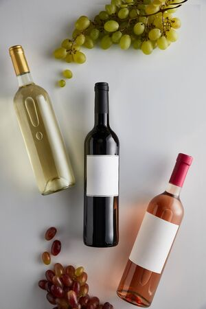 top view of bottles with white, red and rose wine near grape on white background Imagens