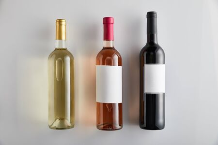flat lay with bottles with white, rose and red wine on white background
