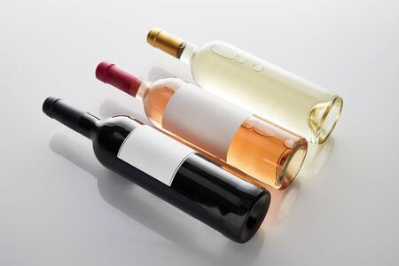 bottles with white, rose and red wine on white background Imagens