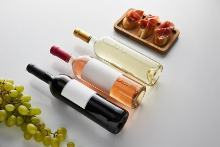 bottles with white, rose and red wine near grape and sliced prosciutto on baguette on white background