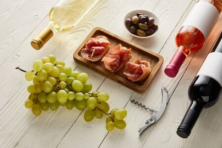 bottles with red, white and rose wine near grape, prosciutto on baguette near olives and corkscrew on white wooden surface