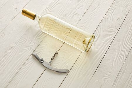 bottle with white wine near corkscrew on white wooden surface