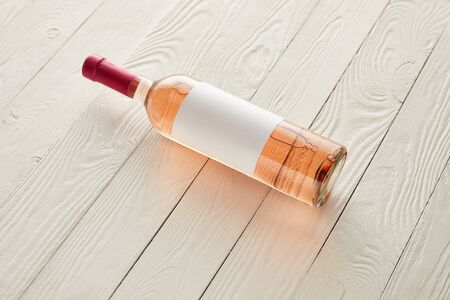 bottle with rose wine and blank label on white wooden surface