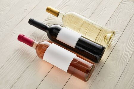 bottles with red, white and rose wine on white wooden surface
