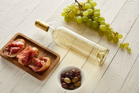 bottle with white wine near grape, prosciutto on baguette, olives on white wooden surface