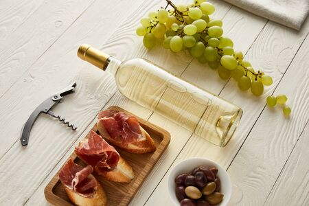 bottle with white wine near grape, prosciutto on baguette, olives and corkscrew on white wooden surface