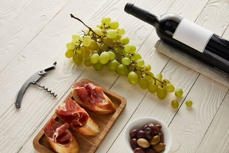 bottle with wine near grape, prosciutto on baguette, olives and corkscrew on white wooden surface