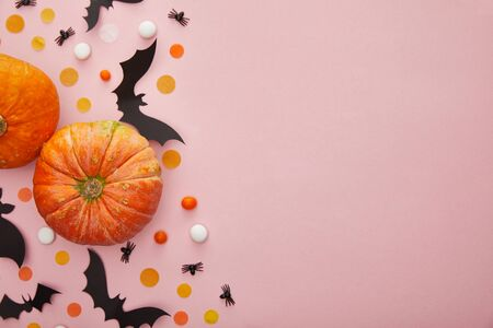top view of pumpkin, bats and spiders with confetti on pink background, Halloween decoration