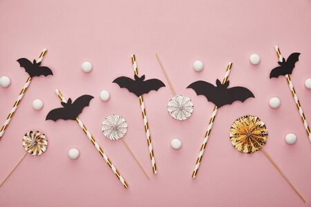 top view of bats on sticks on pink background, Halloween decoration