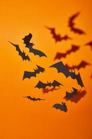 paper bats with shadow on orange background, Halloween decoration Stockfoto