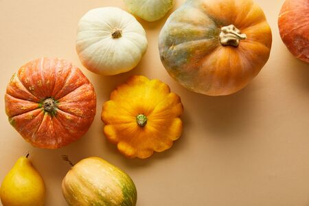 top view of ripe whole colorful pumpkins on beige background