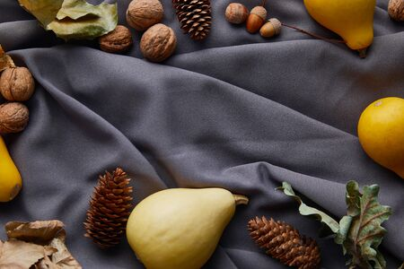 top view of ripe pumpkins and autumnal decor on grey cloth with copy space