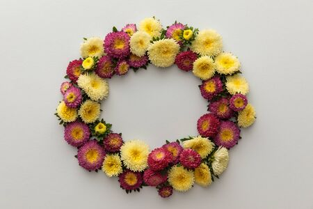 wreath of yellow and purple asters on white background with copy space