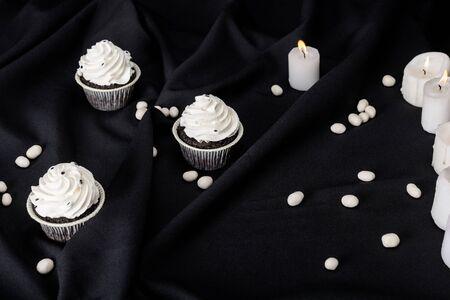 tasty Halloween cupcakes with white cream near burning candles on black cloth Stockfoto