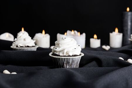 selective focus of tasty Halloween cupcakes with white cream near burning candles isolated on black
