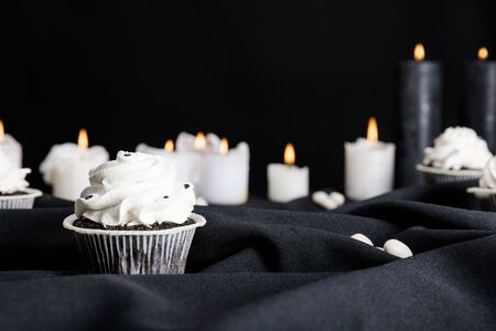selective focus of tasty Halloween cupcake with white cream near burning candles isolated on black
