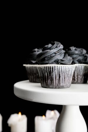 selective focus of burning candles and delicious Halloween cupcakes with black cream isolated on black Stockfoto