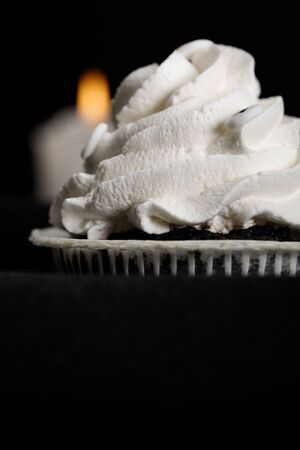 delicious Halloween cupcakes with white cream and blurred candle on background isolated on black Stockfoto