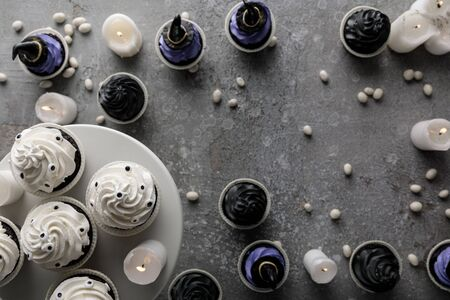 top view of delicious Halloween cupcakes with burning candles on concrete grey surface