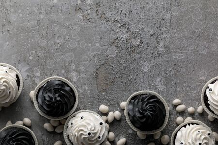 top view of delicious Halloween cupcakes and white sweets on concrete grey surface