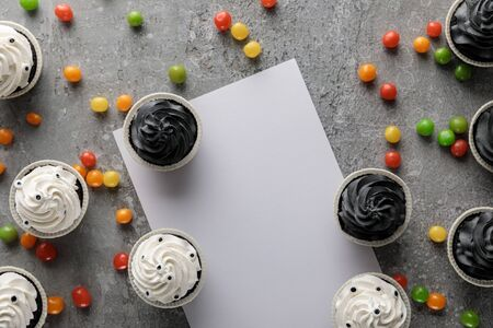 top view of delicious Halloween cupcakes with scattered colorful bonbons near white blank paper on concrete grey surface