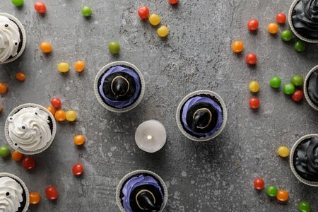 top view of delicious Halloween cupcakes and burning candle with scattered colorful bonbons on concrete grey surface
