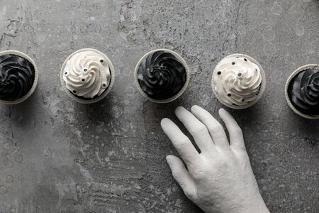 top view of decorative hand near delicious Halloween cupcakes on concrete grey surface Stockfoto