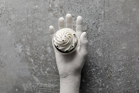 top view of delicious Halloween cupcake in decorative hand on concrete grey surface