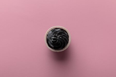 top view of delicious Halloween cupcake with black cream on pink background Stockfoto