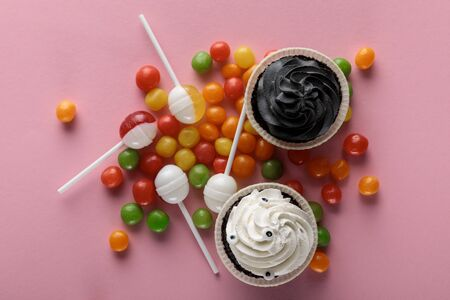 top view of delicious Halloween cupcakes, lollipops and bonbons on pink background Stockfoto