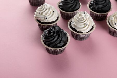 delicious Halloween cupcakes with white and black cream on pink background